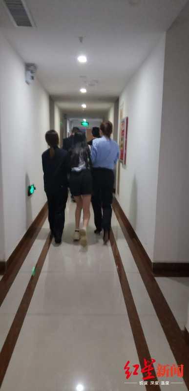 ↑钱某梅坠楼时,警方将缪兰扶着走过酒店走廊