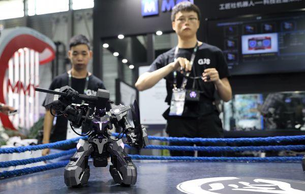 """资料图片: 6月11日,第五届亚洲消费电子展在沪开幕,工作人员(右)在演示一款拥有""""人机一体""""操控技术的竞技格斗机器人。(新华社)"""