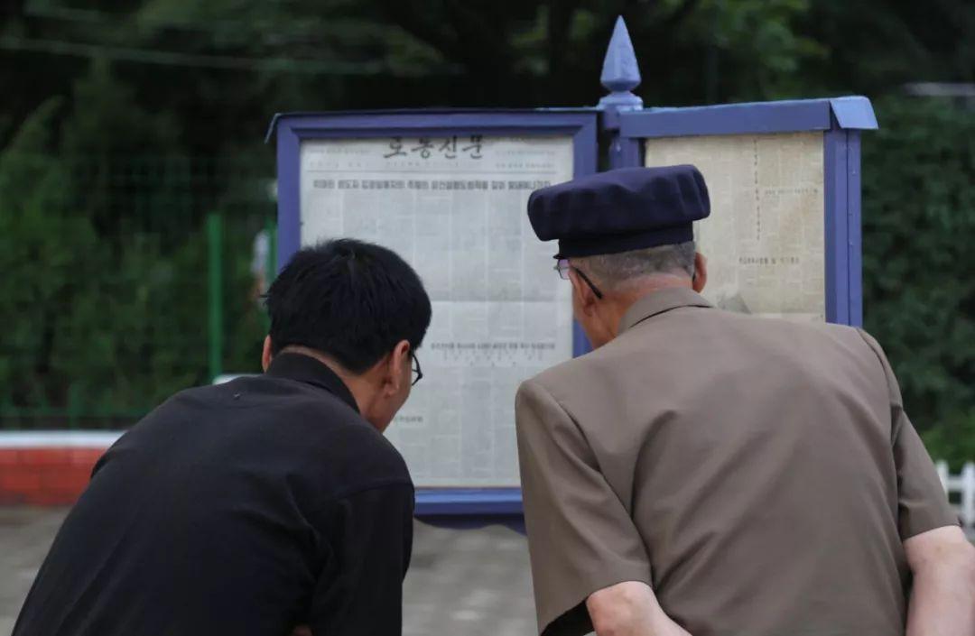 6月19日,在平壤凯旋门附近的一处报纸橱窗前,市民阅读习近平总书记在朝鲜主流媒体《劳动新闻》发表的署名文章。新华社记者江亚平摄