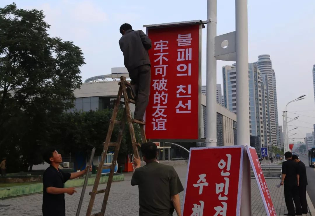 """6月19日,工作人员在平壤街头悬挂使用中朝双语书写的""""牢不可破的友谊""""标语牌。新华社记者江亚平摄"""