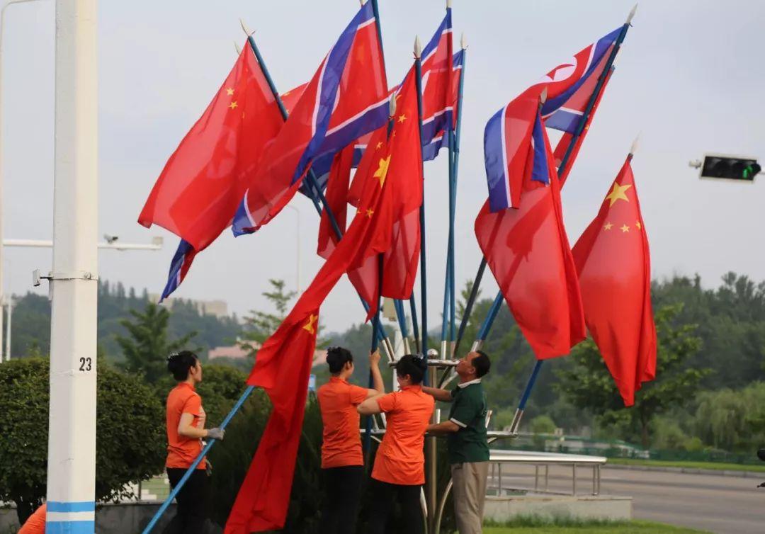 6月19日,当地工作人员在平壤市区街边安装朝中两国国旗。新华社记者江亚平摄