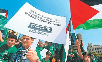 """6月25日,在位于黎巴嫩首都贝鲁特的联合国西亚经济社会委员会总部前举行的示威游行中,一名示威者手举写有反对""""世纪协议""""等口号的牌子。  比拉尔·贾维希摄(新华社发)"""