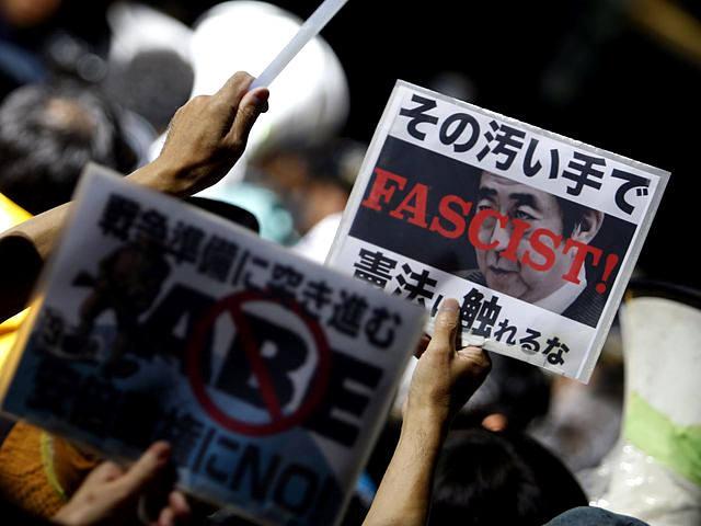 """抗议者举着标语牌,标语牌上印有安倍的头像,并写着""""法西斯!""""字样(路透社)"""
