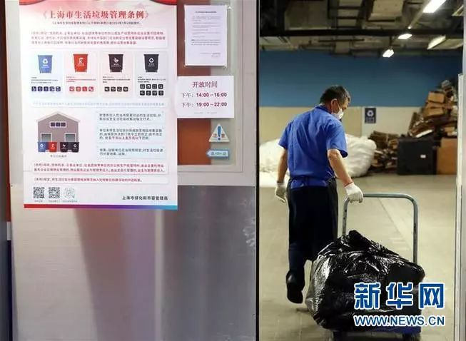 6月19日,上海环球金融中心的垃圾回收人员将垃圾运回垃圾房,进行集中分类整理。新华社记者 刘颖 摄