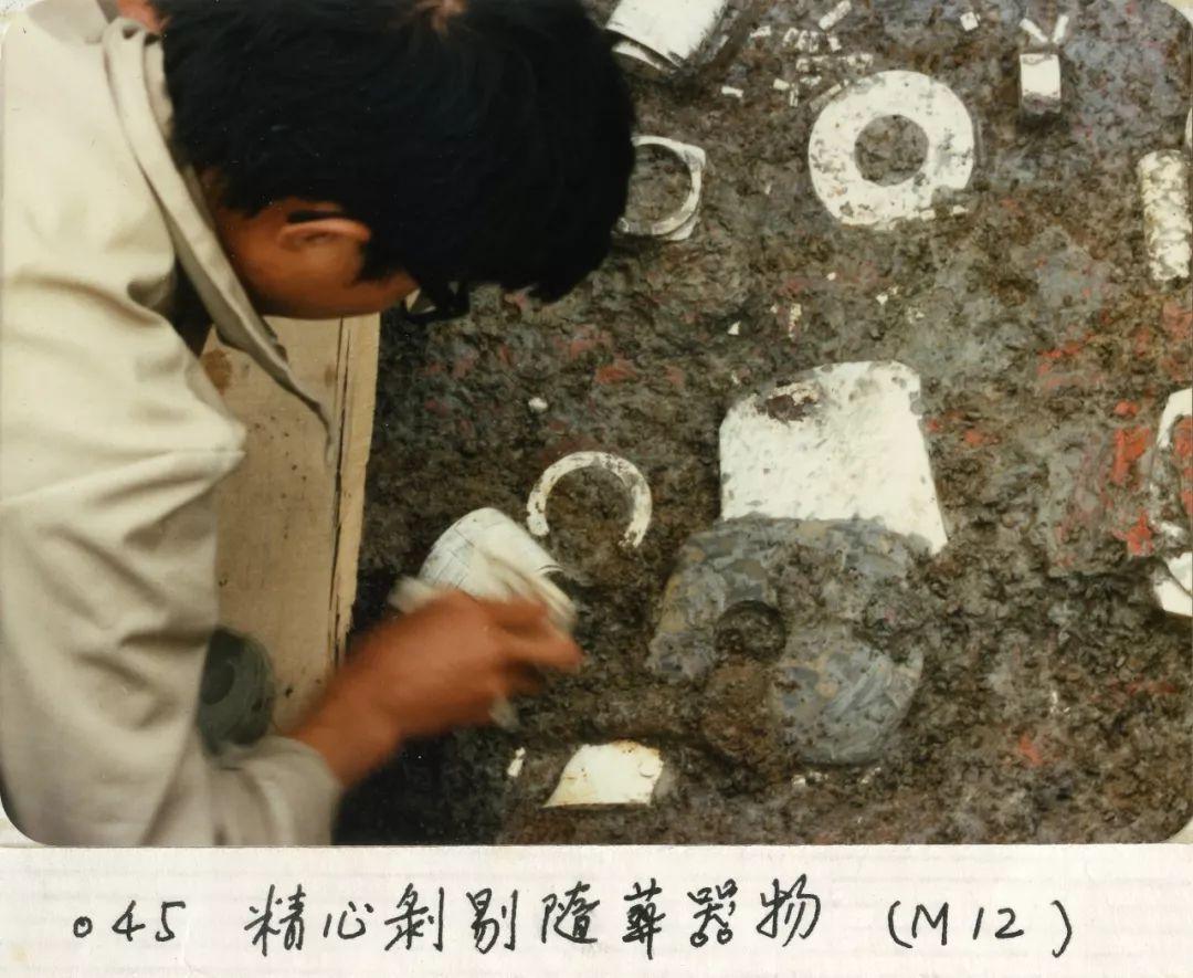 考古专家在剥剔随葬器物。(图片由杭州良渚遗址管理区管理委员会提供)