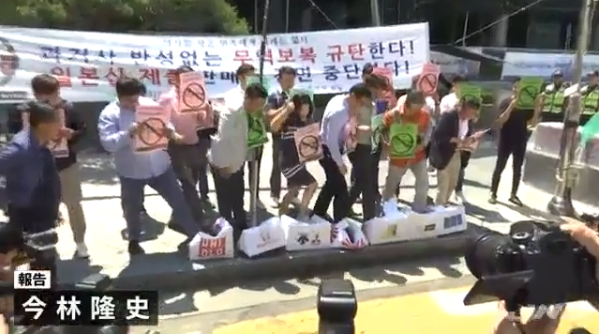 韩国人踩纸箱表示抗议(日本TBS电视台)