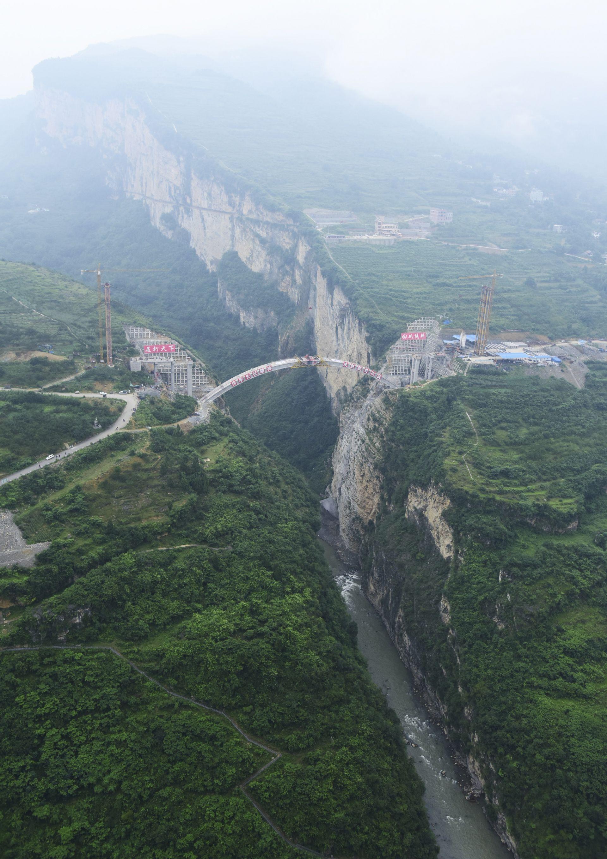 正进行主拱圈合龙施工的鸡鸣三省大桥(新华社)