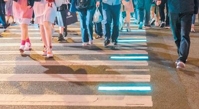 """上海首条会发光人行道在外滩投入使用。人行道上发光地砖的颜色与行人信号灯颜色同步变化:绿灯时,发光地砖显示为闪烁的绿色;红灯时,发光地砖则切换为红色。醒目的颜色能更好地提示行人,尤其是""""低头族""""不要闯红灯。王冈摄(人民视觉)"""