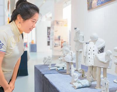 """6月20日,""""新时代·新活力——第六届内蒙古创意设计展""""在位于呼和浩特市的内蒙古展览馆举行,共展出18所院校和协会的1200多组作品。图为观众在欣赏创意设计作品《低头族》。丁根厚摄(人民视觉)"""