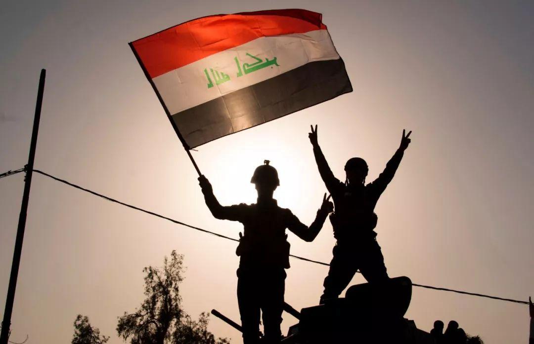 2017年7月9日,在伊拉克摩苏尔,联邦警察部队成员挥舞国旗庆祝摩苏尔战役取得胜利。新华社/法新
