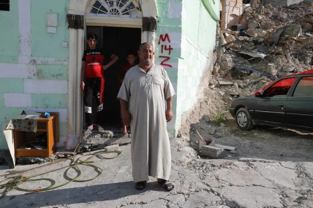2019年7月3日,在伊拉克摩苏尔老城,纳吉姆站在自己未被摧毁的房屋门口。新华社发(哈利勒·达伍德摄)