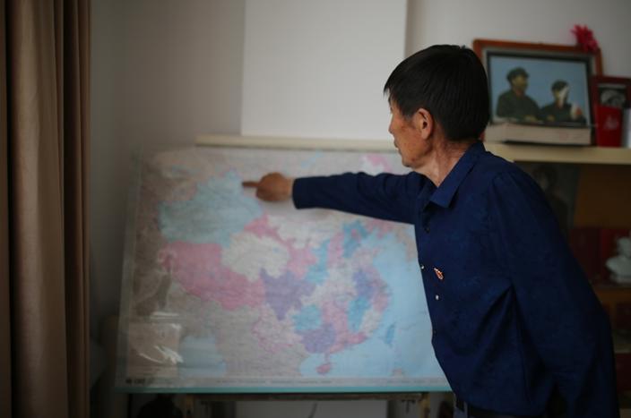巴哈提别克·加斯木汗给记者指可可托海的地理位置。范凌志摄