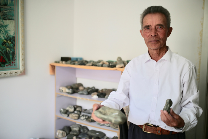 80岁的老矿工艾达尔汗·恰勒哈尔拜给记者看他收集的奇形怪状的石块儿。范凌志摄