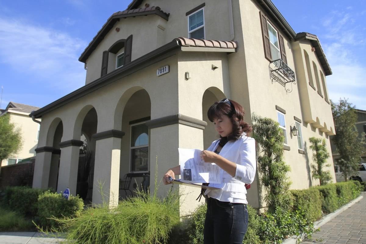 一名专注中国购房者的经纪人在南加州奇诺市的一处房产前 图自《南华早报》