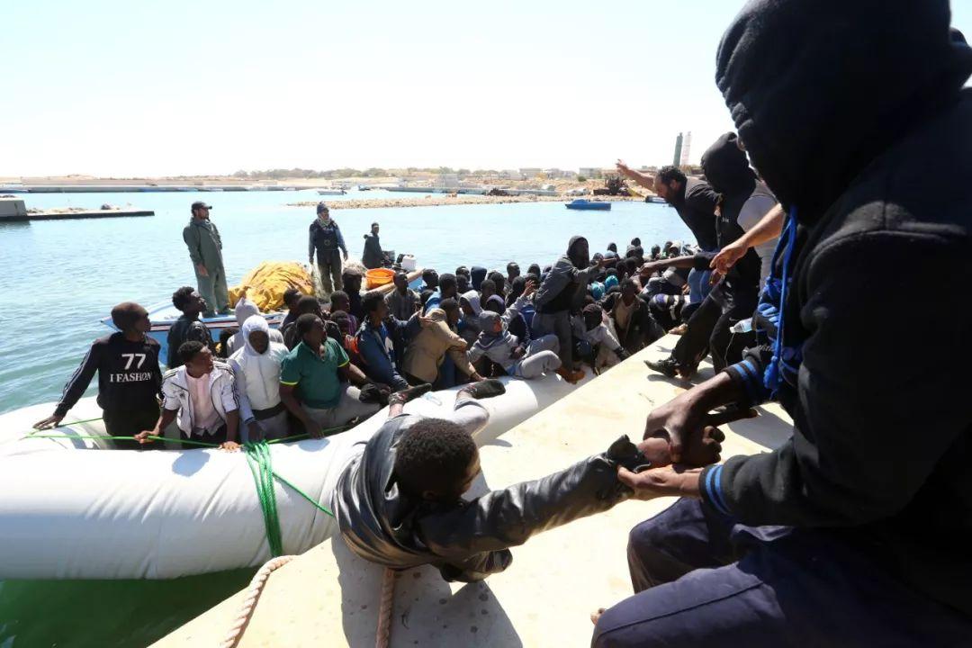 2017年5月18日,在利比亚加拉布里,救济 职员帮忙不法移民登岸。新华网发(哈姆扎·图尔基亚摄)