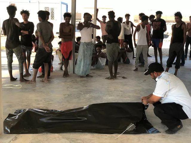 2019年7月25日,在利比亚科马斯,得救的不法移民看着工作职员处置死去移民的尸首。新华网/路透