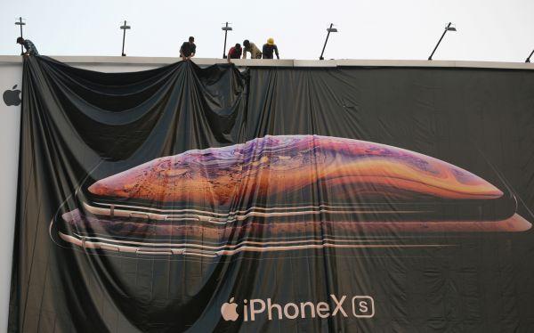 资料图片:印度艾哈迈达巴德,工人正在调整苹果iPhone X的宣传海报。(路透社)