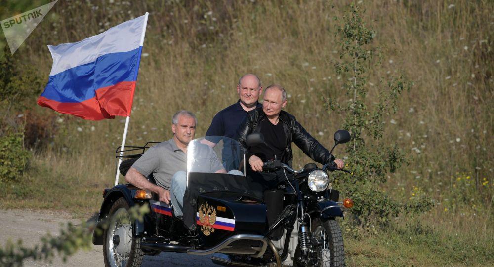 普京骑摩托车带两人出现在车展上(图源:俄罗斯卫星网)