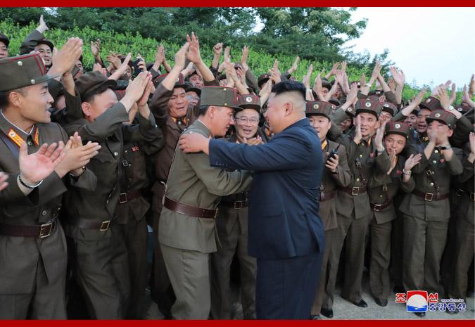 6日,金正恩观摩新型战术导弹发射后,与现场人员庆祝(朝中社)