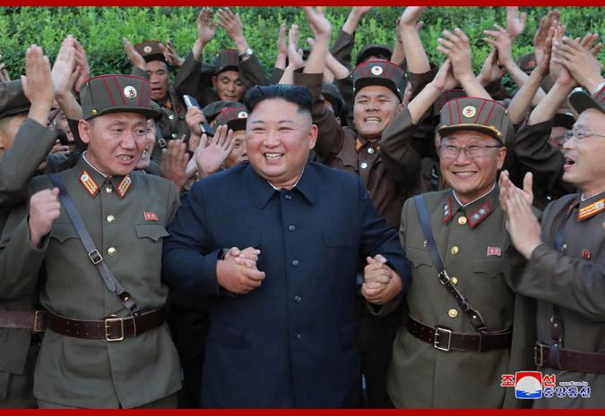 6日,金正恩观摩新型战术导弹发射后,与现场人员合影(朝中社)