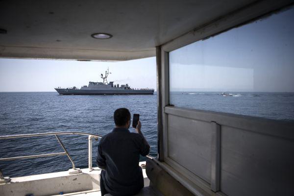 资料图片:2019年4月30日,一名男子用手机拍摄在霍尔木兹海峡巡逻的伊朗军舰。新华社发