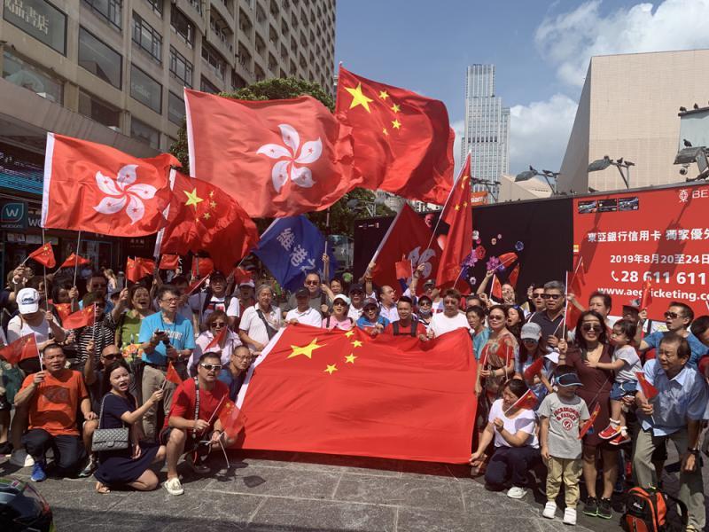 尖沙咀五支旗杆旁高举中国国旗和香港特别行政区区旗(图源:大公报)