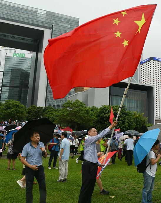 有市民在现场摇曳国旗(图源:《香港商报》)