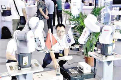 图为青岛宝佳科技公司的技术人员在2019世界工业互联网产业大会上演示智能双联机器人。记者 苏万明 摄