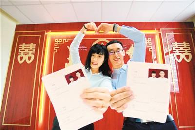 8月7日,在江苏省扬州市广陵区民政局婚姻登记处,一对新人展示刚领取的结婚证。孟德龙摄(人民视觉)