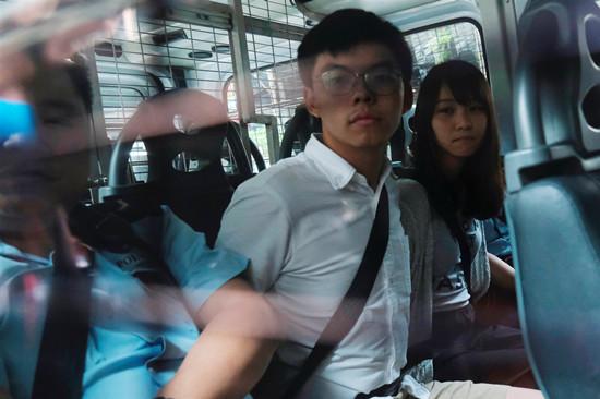 图为黄之锋(中)8月30日被捕,由警车押送到东区裁判法院提堂。