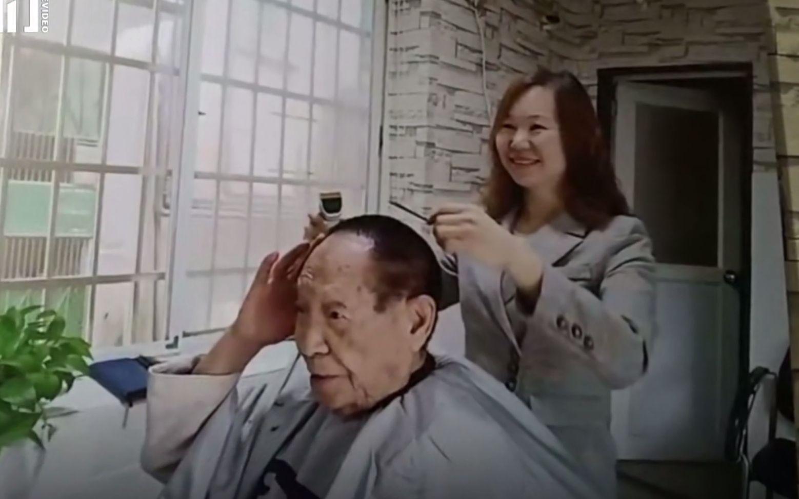 店内悬挂的曹小萍为袁隆平理发的照片。 新京报我们视频截图