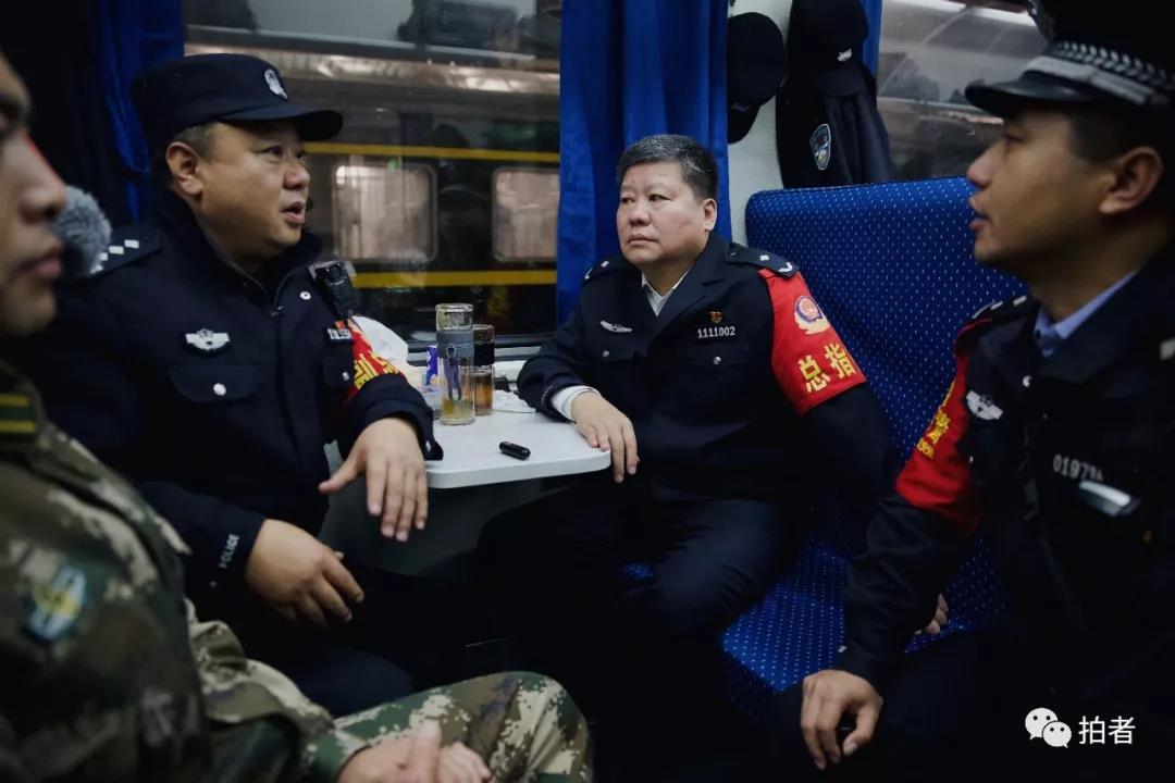 △12月4日,负责遣送的民警在列车车厢内开会。