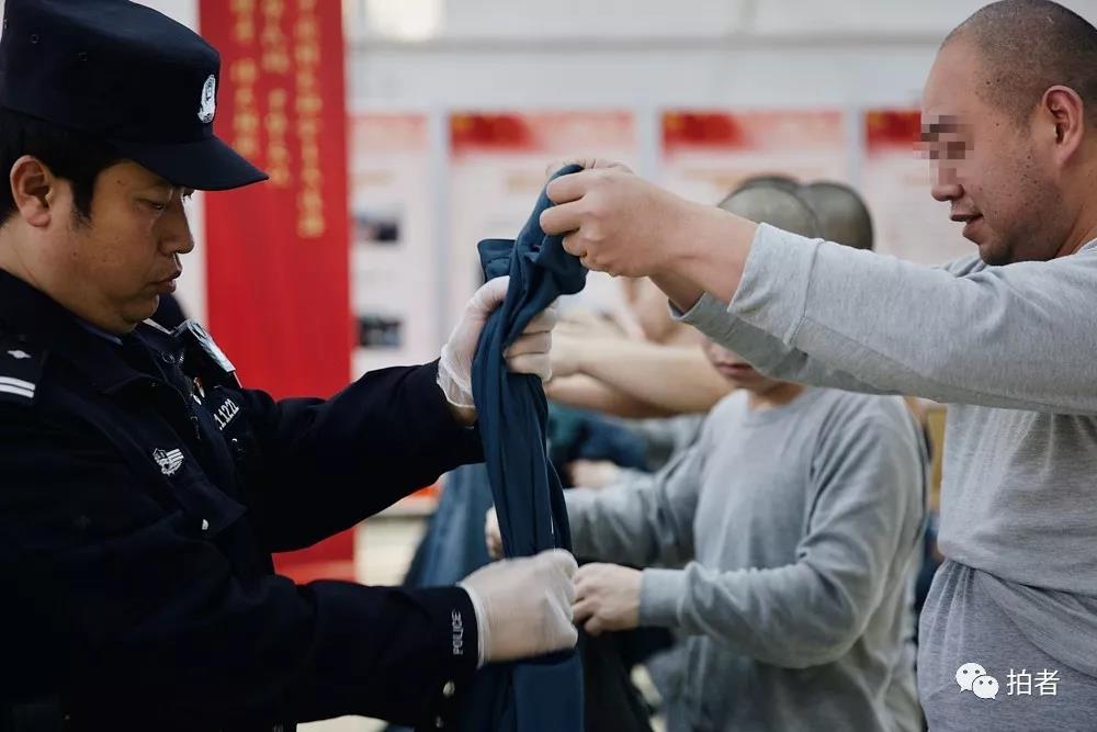 """△12月4日,天河监狱,""""清身""""是指出发前对服刑人员的全面清查。民警把服刑人员所穿的衣服鞋袜,包括可能藏有细小物品的耳朵、嘴巴,都挨个检查一遍,防止夹带违禁物品。"""