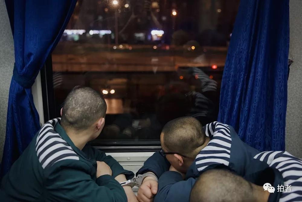 △12月4日,列车开动,服刑人员看着车窗外的车水马龙。