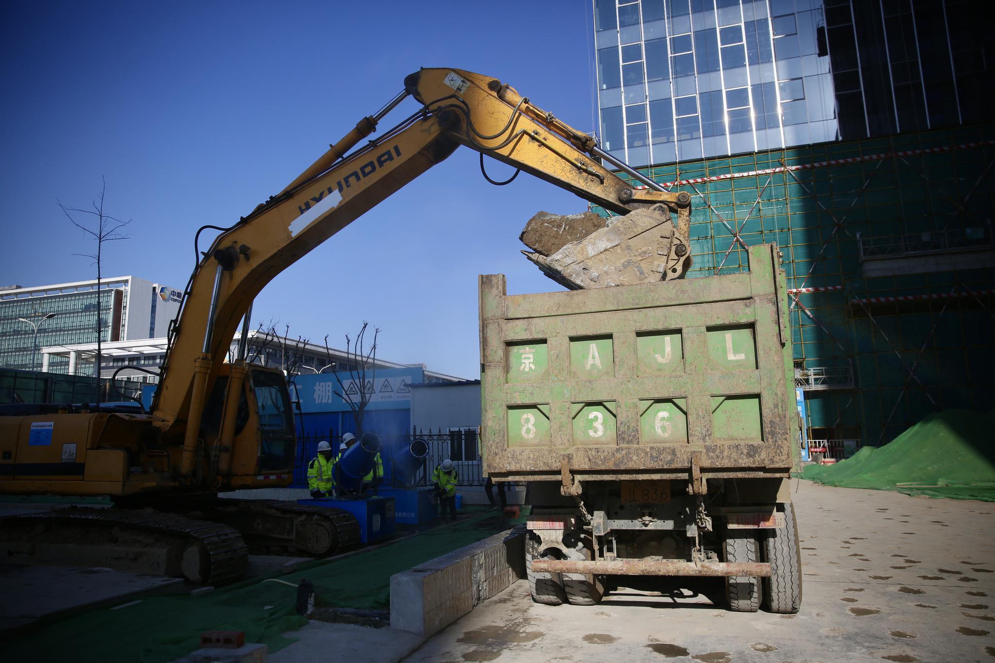工人将分好的建筑垃圾装车运往渣土消纳场。摄影/新京报记者 郑新洽