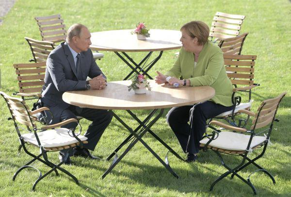 """资料图片:2018年8月18日,德国总理默克尔(右)与来访的俄罗斯总统普京进行会谈。双方就""""北流-2""""天然气管道项目等棘手问题进行讨论。(新华社/美联)"""