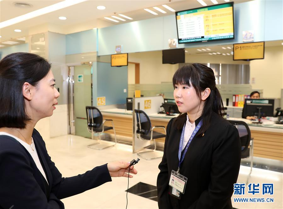 12月19日,陈殷桁(右)在澳门黑沙环政府综合服务中心接受采访。新华社记者 李钢 摄