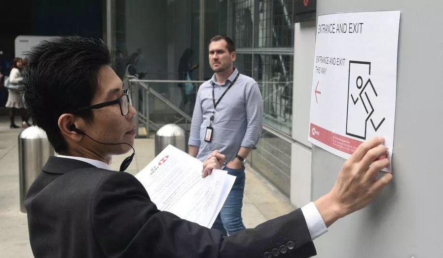 汇丰职员正在门口贴告示,指示可用收支口 港媒图