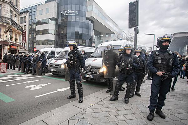 12月17日,在法国北部城市里尔,警察在示威游走现场警戒。 新华社图