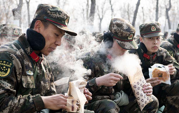 12月25日正午,武警官兵在一处汜博的草丛中就地休休,拿出自炎食品和干粮增添体力。