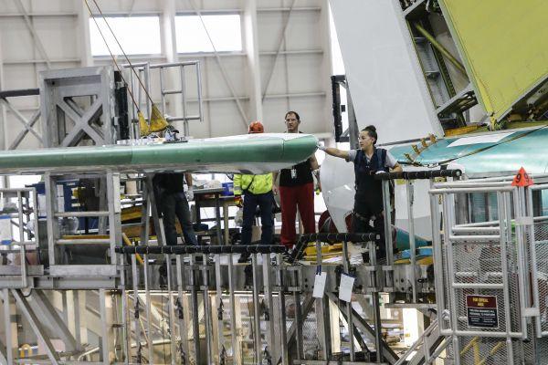 原料图片:工人们在美国华盛顿州的波音埃弗里特工厂的737单通道飞机生产线上吊装一架飞机的尾翼。(新华社)