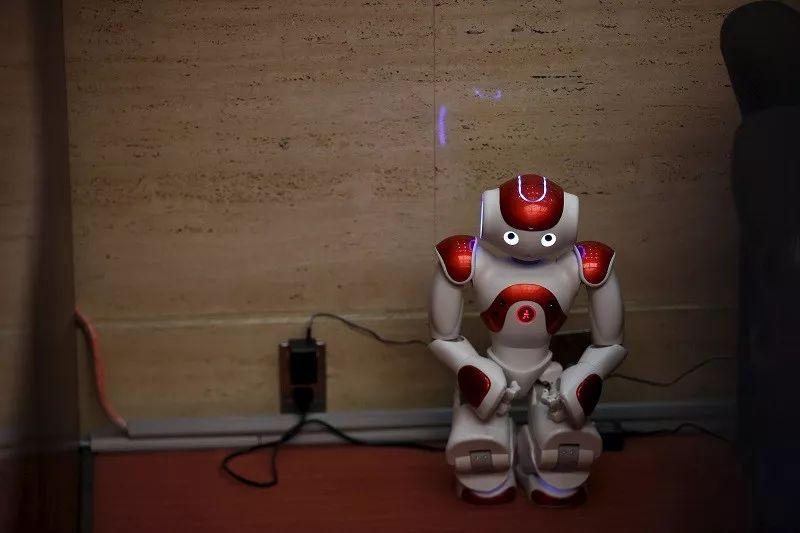 """▲资料图片:在日本东京的三菱东京UFJ银行支行,一个""""Nao""""机器人蹲在墙边充电。这个机器人能够用日语、英语和中文向顾客讲解银行业务。(新华社)"""
