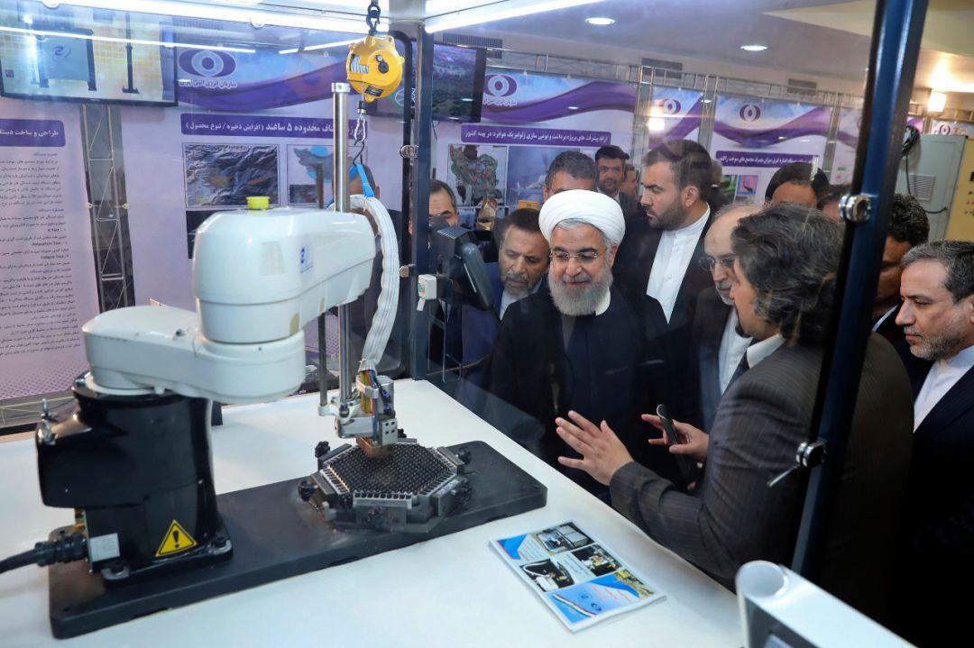 4月9日,伊朗总统鲁哈尼(中)在一场纪念活动上听取有关核成就的讲解。鲁哈尼当天说,伊朗无论如何都将继续推进核技术发展。(新华社/美联)