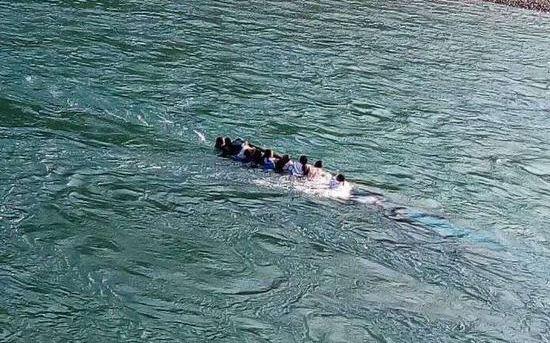 翻船后多人抓扶已被淹没的船舶。受访者供图