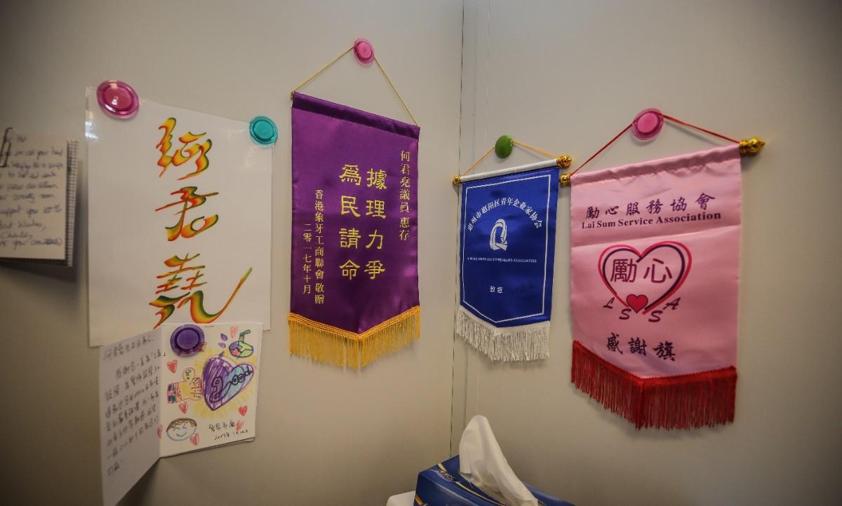 图为一些社会团体送来的锦旗和感谢信挂在何君尧的办公室内。