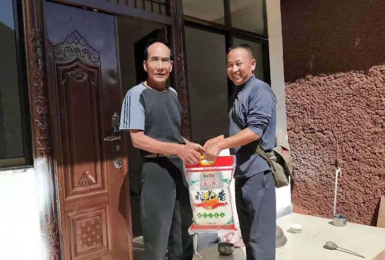 李兴富(右)生前到村民家开展工作。 受访者供图