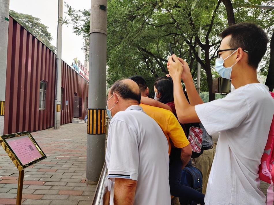 北京十八中附属实验小学门前,家长们在通过指示牌确认孩子所属班级。