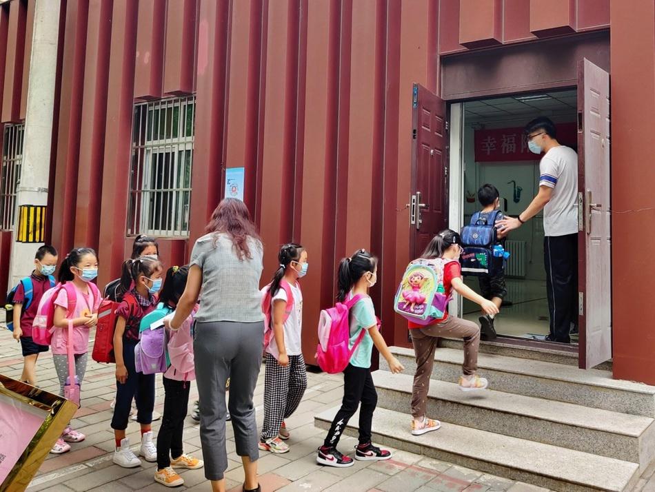 北京十八中附属实验小学新生在老师的引导下走进校门。
