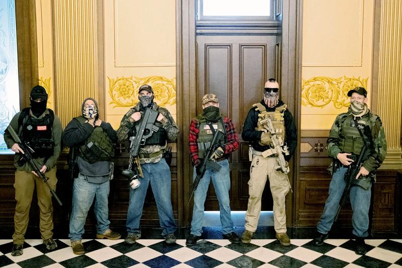 △今年4月,持枪抗议者进入密休根州议会大厦,并守在惠特默办公室门口(图片来源:路透社)