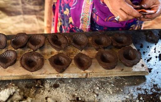 印度妇女们在排灯节前用牛粪和泥混合制作油灯(法新社)